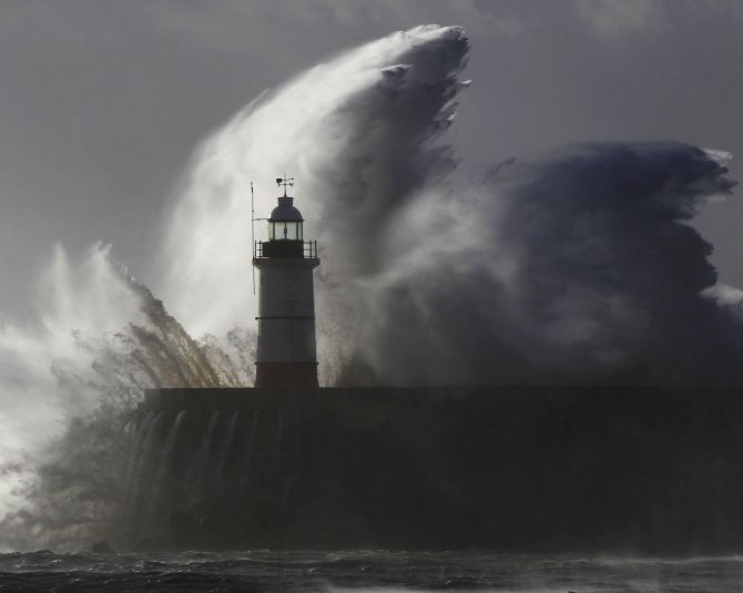 Huge waves crash against a lighthouse as s