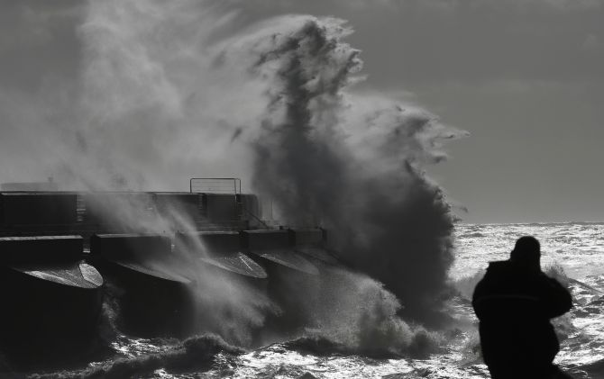 A man watches stormy seas in strong winds as waves crash on the harbour wall at Brighton marina in south east England on Monday