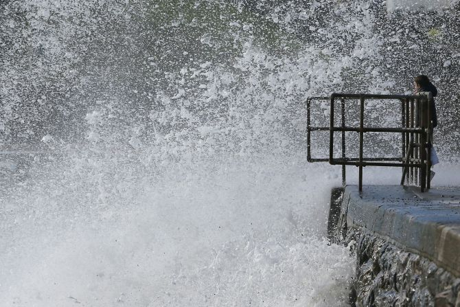 A young boy watches as waves crash against the seafront at Dawlish in Devon, on Monday.