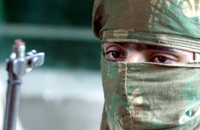 A masked terrorist looks on during a surrender ceremony