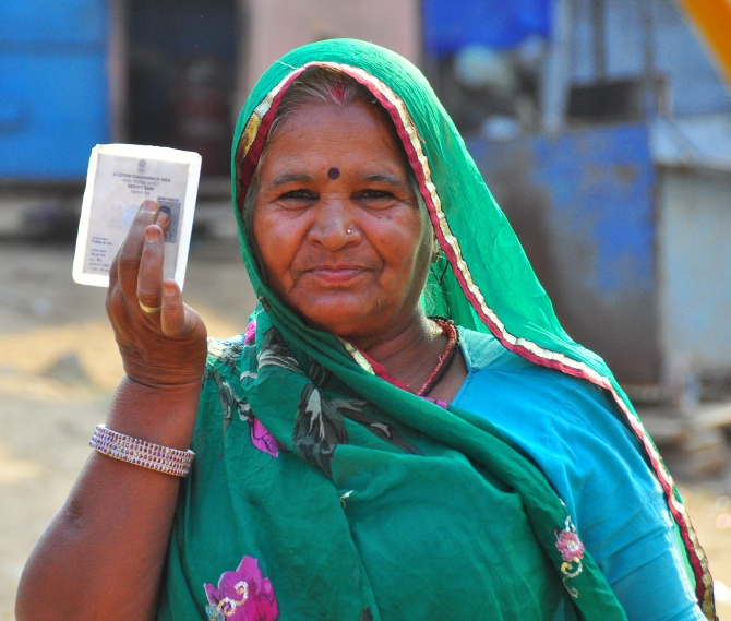 A woman voter shows her voter identity card