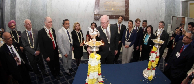 Congressman Joe Crowley lights the diya as US Representative for California Dr Amerish 'Ami' Bera and Tulsi Gabbard look on with others