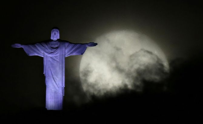 The moon is pictured next to the Christ the Redeemer statue in Rio de Janeiro