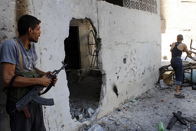 Free Syrian Army fighters take positions as one of them fires his weapon towards what they say are snipers loyal to Syria's President Bashar al-Assad in the old city of Aleppo