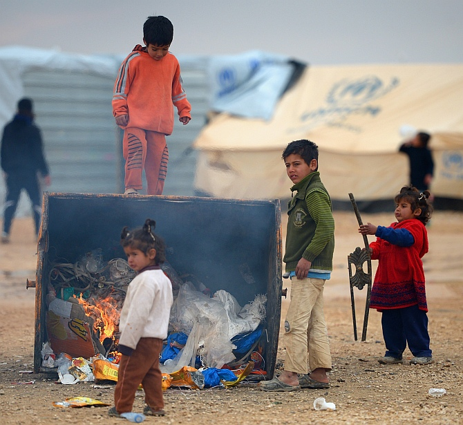 Young children get heat from a burning rubbish bin as Syrian refugees go about their daily business in the Za'atari refugee camp in Jordan