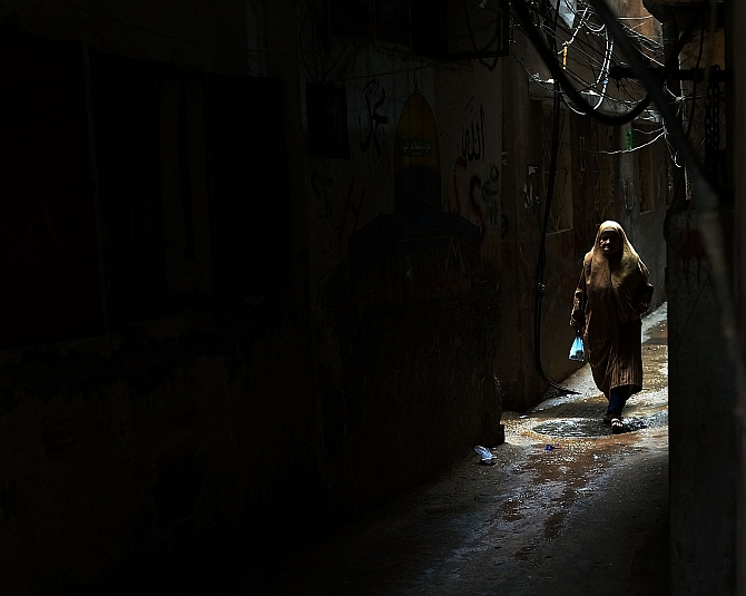 A woman walks down an alley in a poor neighborhood with a high concentration of Syrian refugees in Beirut, Lebanon