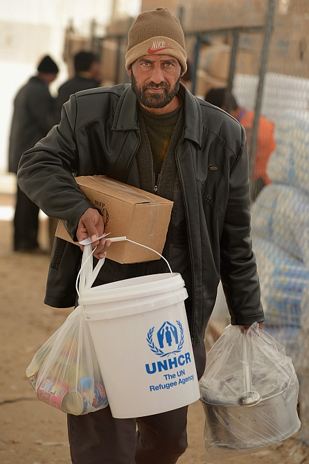A refugee from Syria collects food and supplies from the UNHCR as he arrives at the Za'atari refugee camp in Mafrq, Jordan