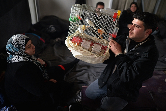 A man shows off his pet birds as new Syrian refugees arrive at the International Organisation for Migration at the Za'atari refugee camp in Mafrq, Jordan
