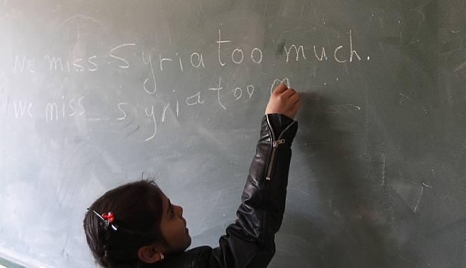 A Syrian refugee girl writes we miss Syria too much on the chalkboard in her classroom in Majdel Anjar in Bekaa Valley