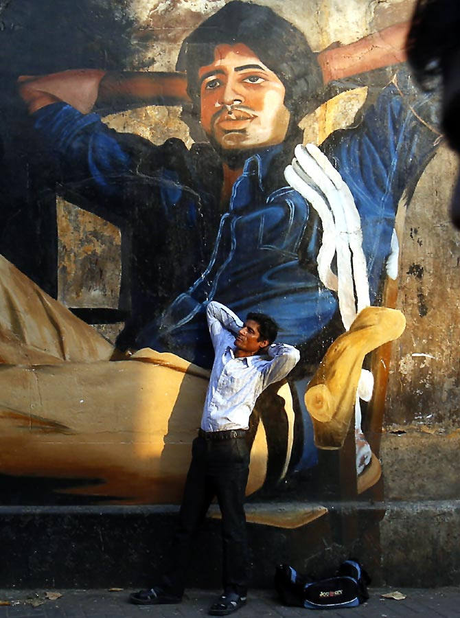 Ram Pratap Verma, an aspiring Bollywood actor, poses in front of a mural of Superstar Amitabh Bachchan.