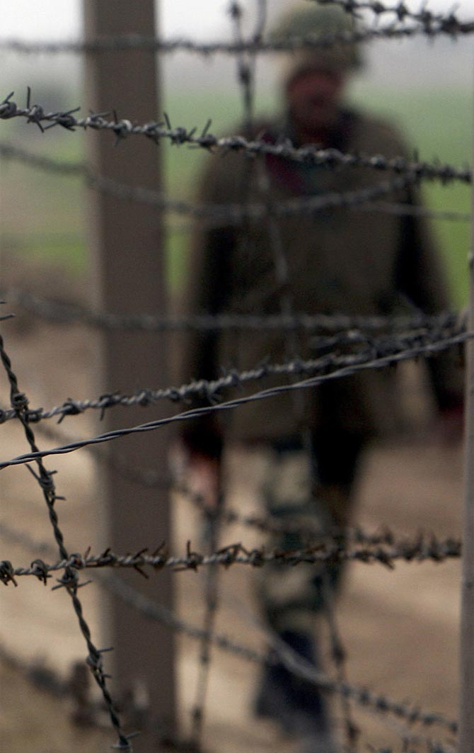 A BSF soldier patrols near the fenced border with Pakistan in Suchetgarh, southwest of Jammu