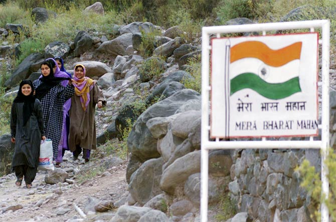 Kashmiri village girls walk near a signboard that reads: 'My India (is) Great'