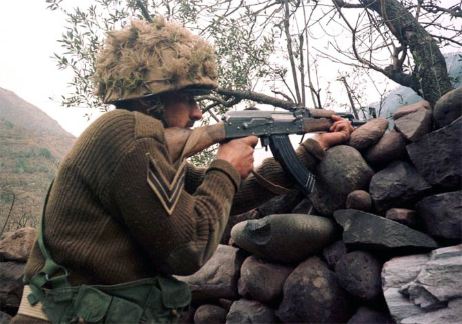 A Pakistani soldier aims his rifle towards Kashmir at his position on the Line of Control  in Chakoti