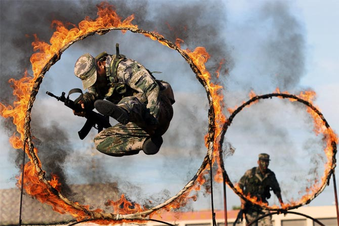 A soldier from the People's Liberation Army jumps through a ring of fire as part of training during the PLA Army Day in Wenzhou, Zhejiang province