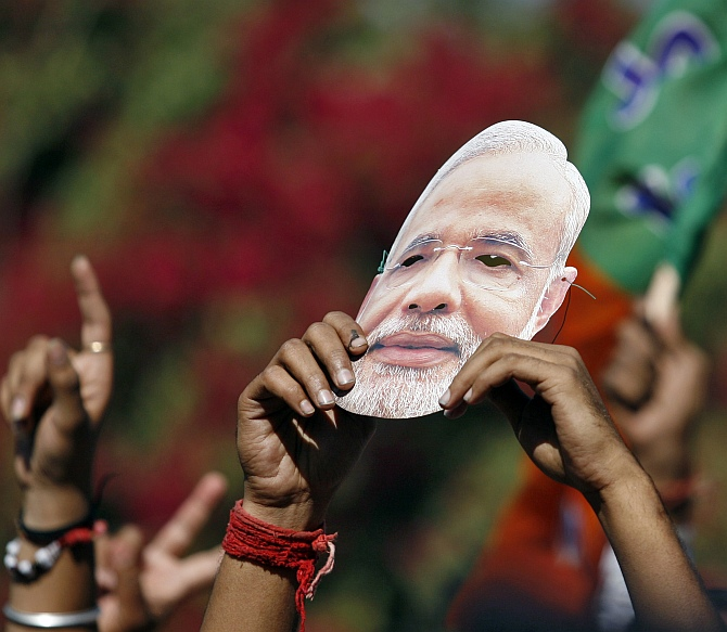 A Bharatiya Janata Party supporter holds a mask of Modi during a celebration outside a vote counting centre in Ahmedabad
