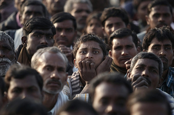 Congress supporters listen to a speech by Rahul Gandhi during an election campaign rally at Hardoi district in Uttar Pradesh