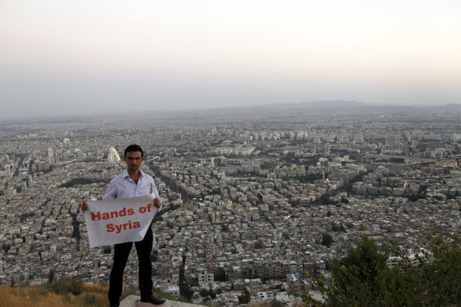 A supporter of Syria's President Bashar al-Assad holds a placard during his participation with others in 'Over our Bodies', a campaign to organise human shields against possible US strikes, at Qasion Mountain overlooking the capital Damascus
