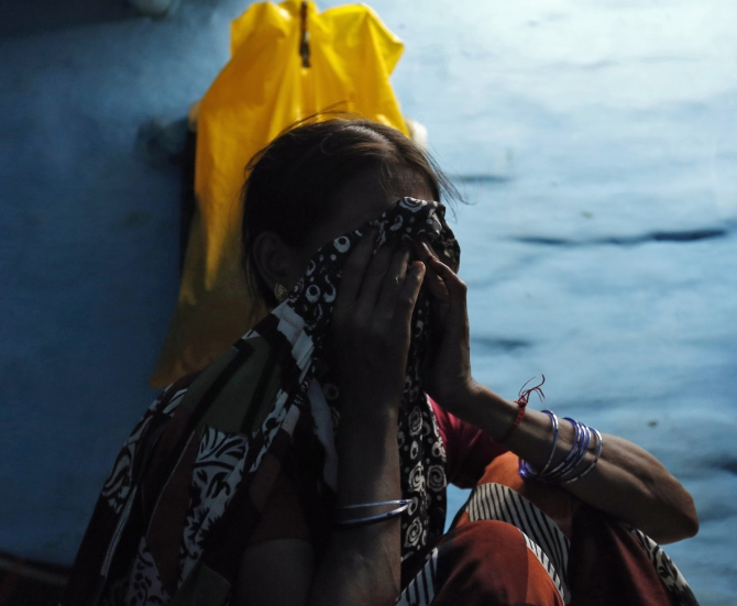 The mother of one of the four men, found guilty of the fatal gang-rape of a young woman on a bus in New Delhi last year, cries upon seeing the news on a court verdict on a TV inside her house at a slum in New Delhi