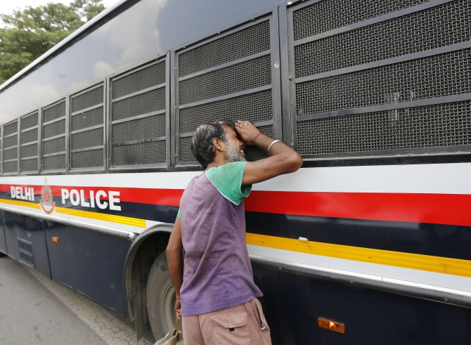 A man peeks into the police vehicle carrying four men, who were found guilty of the Delhi gang rape