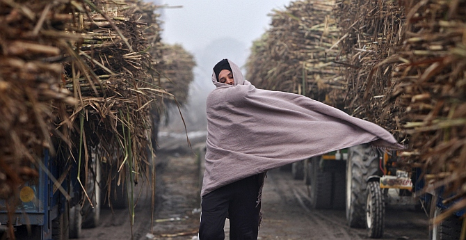 A farmer covers himself with a shawl on a cold winter day outside a sugar mill at Morinda, in Punjab