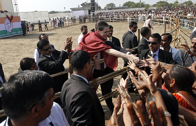 Congress president Sonia Gandhi shakes hands with people during an election campaign in Gujarat
