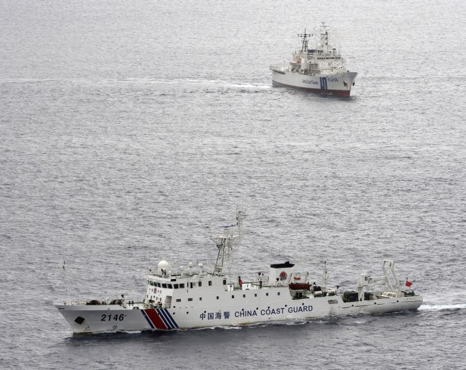 A China Coast Guard vessel (front) sails near a Japan Coast Guard vessel in the South China Sea