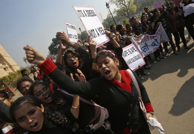 Demonstrators shout slogans as they hold placards in front of the India Gate demanding justice in the Delhi gang rape case