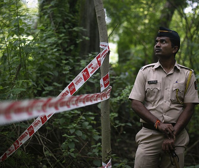 A policeman stands guard near the crime scene where a photo journalist was raped by five men inside an abandoned textile mill in Mumbai