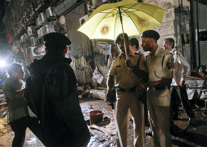 Policemen stand guard at the site of an explosion near Opera House in Mumbai