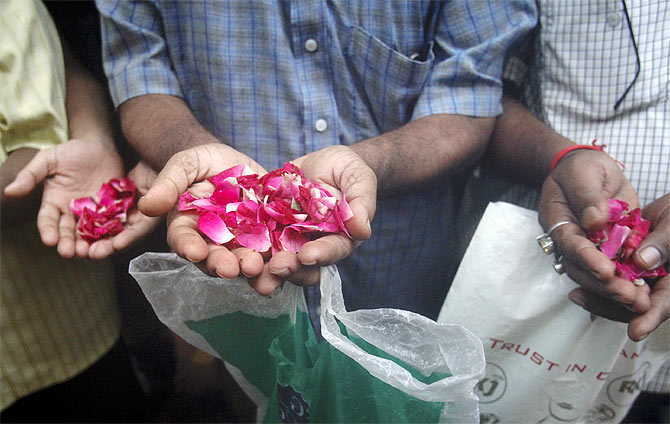 Residents carry rose petals to scatter at the entrance of Zaveri Bazaar, one of the sites of triple explosions in Mumbai