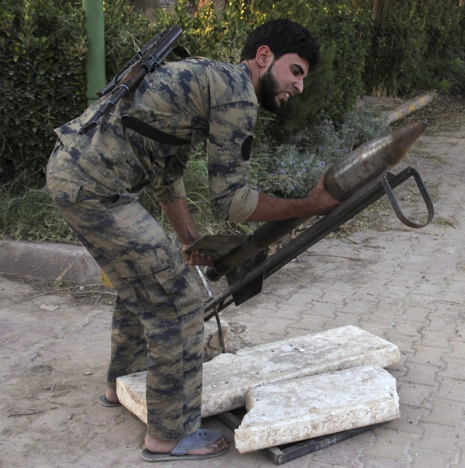 A Free Syrian Army fighter prepares a homemade rocket in Deir al-Zor