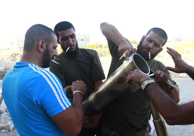 Free Syrian Army fighters smoke cigarettes as they prepare a mortar launcher near Nairab military airport, which is controlled by forces loyal to Syria's President Bashar al-Assad, in Aleppo