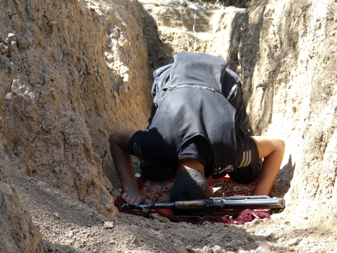 A Free Syrian Army fighter prays near a weapon in a trench in Al-Maliha, Damascus suburbs