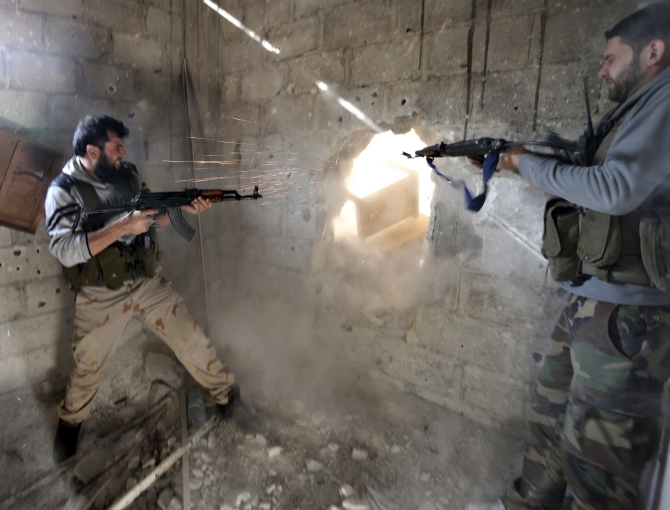 Fighters from the Free Syrian Army's Tahrir al Sham brigade fire at Syrian army positions during heavy fighting in Mleha suburb of Damascus