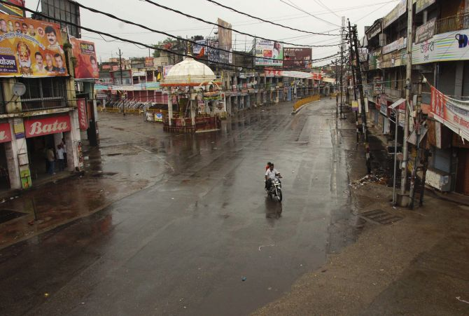 A man rides his motorbike on a deserted street during a curfew in Muzaffarnagar.