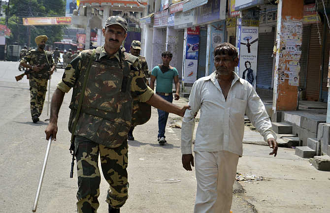 Security personnel detain two men for questioning during a curfew in Muzaffarnagar after the communal violence in September 2013.