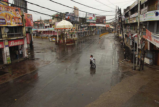 A man rides his motorbike on a deserted street during curfew in Muzaffarnagar. Political parties have exploited the situation to secure their vote