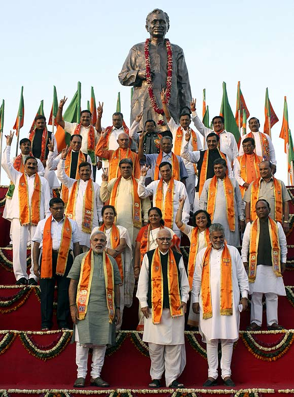 BJP leader Lal Krishna Advani and Gujarat's Chief Minister pose with their party candidates during an election campaign in Ahmedabad. At the back is a statue of Pandit Deendayal Upadhyaya