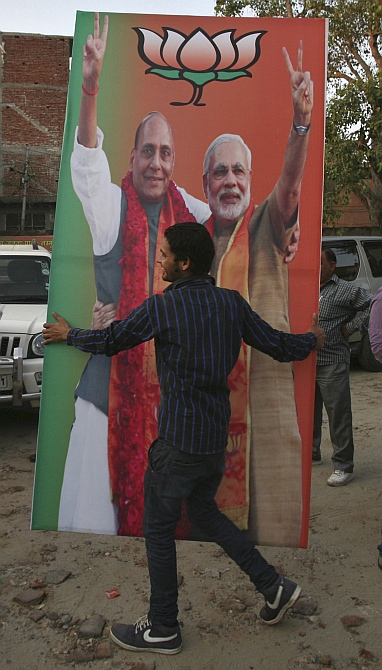 An activist of the Bharatiya Janata Party carries a hoarding featuring Gujarat Chief Minister Narendra Modi and Rajnath Singh, president of the BJP, during celebrations before Modi was crowned as the prime ministerial candidate for the party, in Jammu