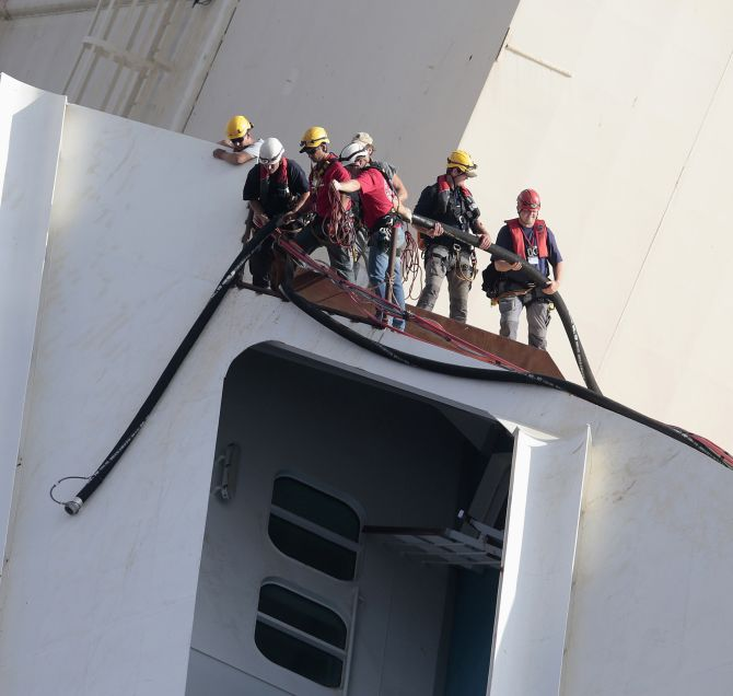 Salvage crew workers work on a side of the capsized Costa Concordia cruise liner outside Giglio harbour.