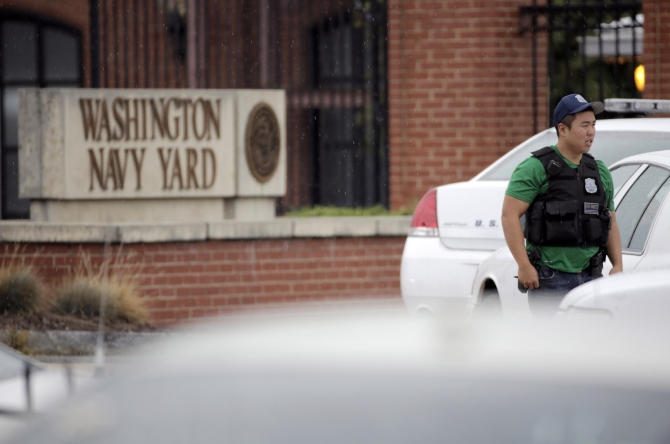 A law enforcement officer keeps bystanders back from the scene of a shooting at the Washington Navy Yard