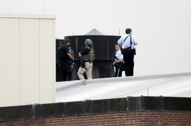 Law enforcement officers are deployed on a rooftop as they respond to a shooting on the base at the Navy Yard