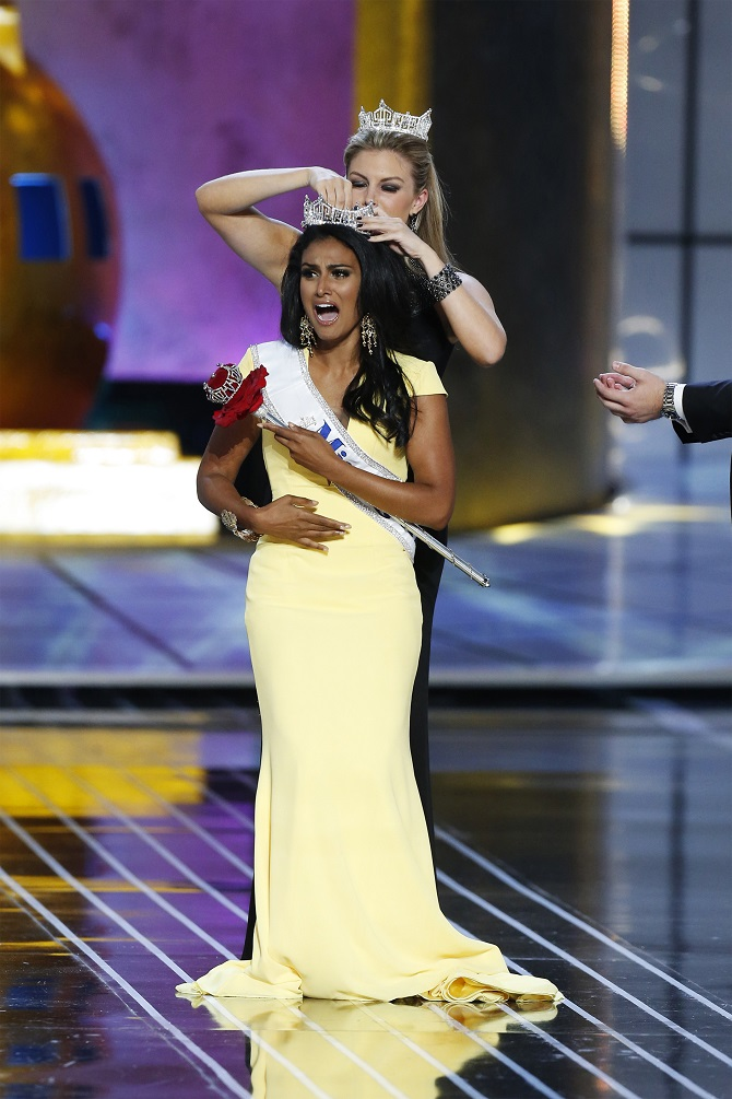 Miss America contestant, Miss New York Nina Davuluri reacts after being chosen winner of the 2014 Miss America Pageant as 2013 Miss America Mallory Hagan places a tiara on her head in Atlantic City, New Jersey