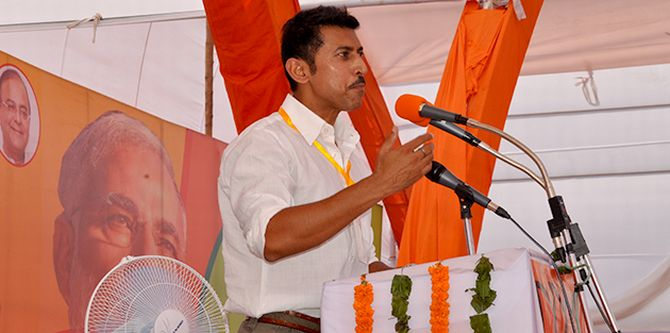 Olympics gold medalist Rajyavardhan Rathore speaking to BJP supporters in Rewari, Haryana alongside Narendra Modi