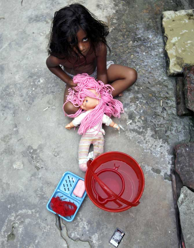 A girl playing with her doll looks on outside her house at a slum in New Delhi