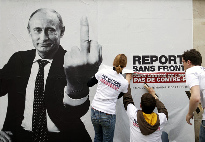 Activists from Reporters Without Borders paste a poster depicting Russia's President Vladimir Putin to mark the 20th annual World Press Freedom day