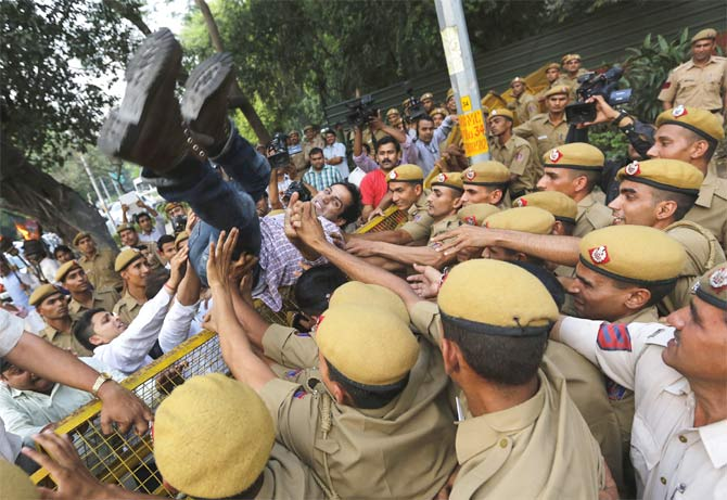 Policemen push a protester during a demonstration against the rising cases of rape in Delhi