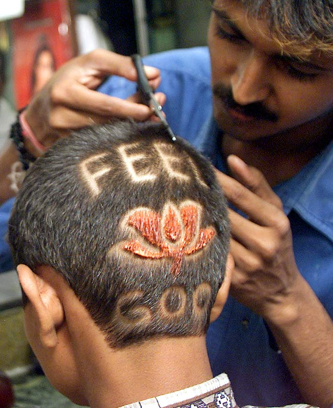 A barber applies finishing touches to a lotus hairstyle he designed for a supporter of the BJP