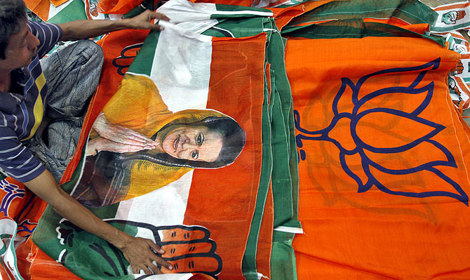 A worker looks at a Congress party flag carrying a picture of its party chief Sonia Gandhi next to flags of the BJP  inside an election campaigning material workshop