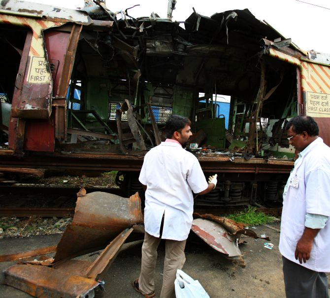 Forensics examine a train compartment destroyed by the serial blasts in Mumbai in 2006